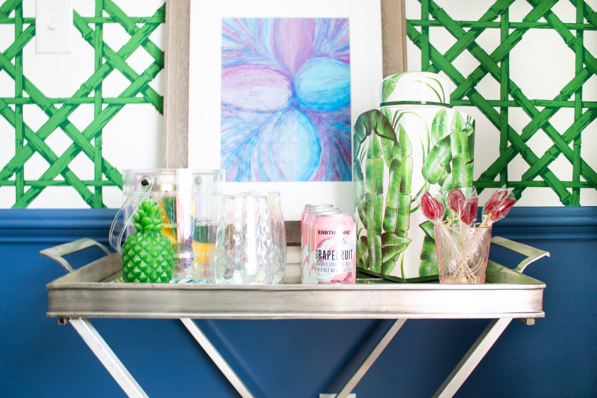 Silver bar cart in dining room against the wall with green wallpaper and artwork. The bar cart has drinks and glassware.