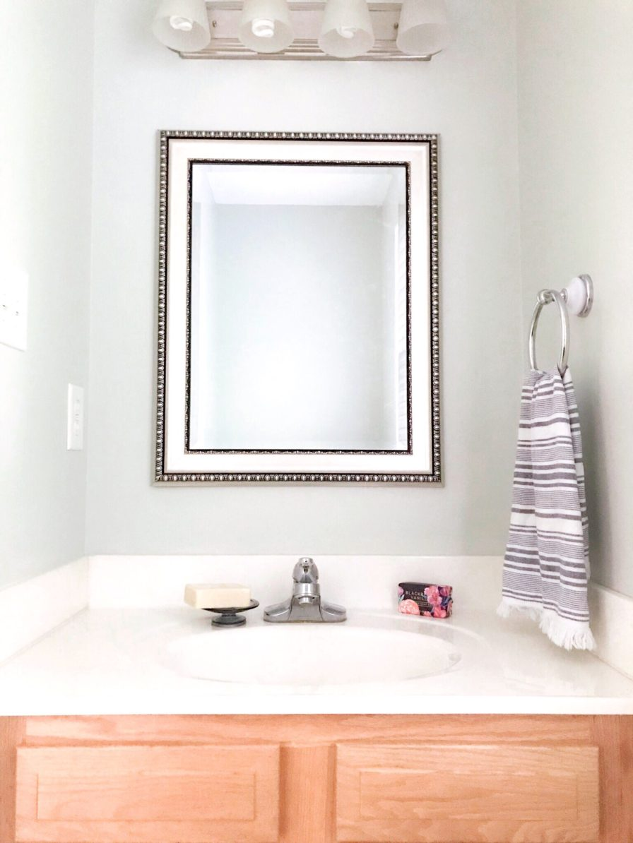builder grade bathroom with new mirror and Sherwin Williams Sea Salt painted walls