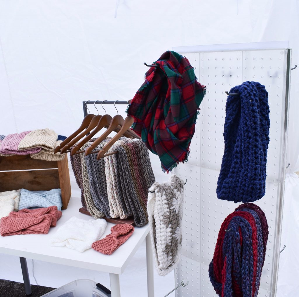 handmade knit scarves hanging on wooden hangers at a craft fair