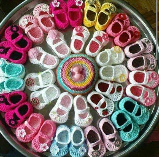 colorful knitted baby booties displayed in a circle