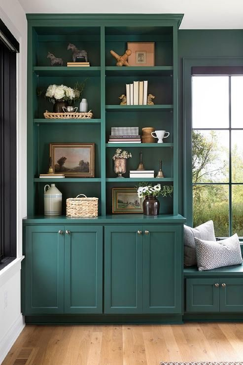 Home office with green built in bookcases and a window seat.
