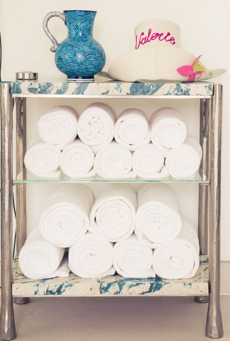 Roll white towels and stash them on a bar cart for ideal bathroom storage