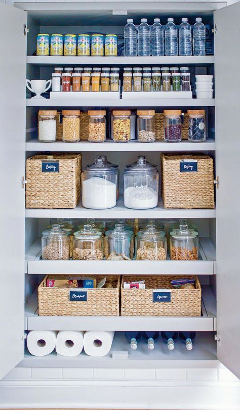 This Pantry by The Home Edit is Organized with baskets and clear jars.