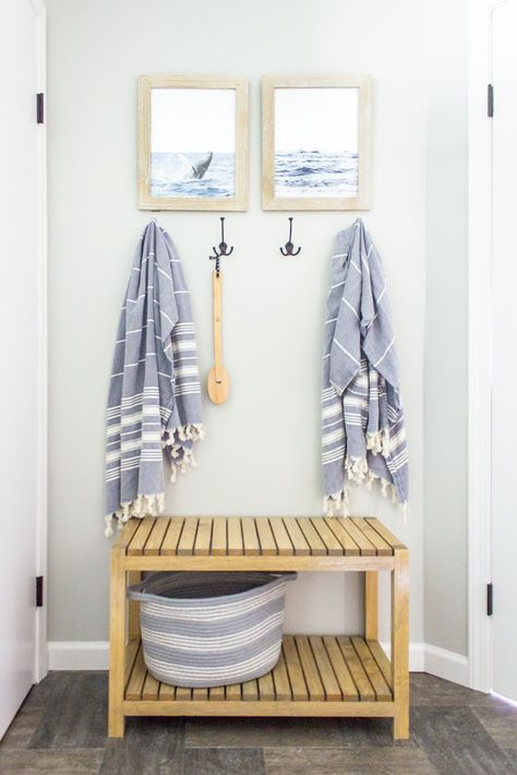 A bench and hooks provide a place for towels to dry and storage for bathroom essentials.