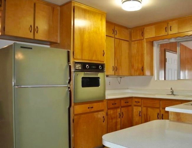 This image has an empty alt attribute; its file name is classic-70s-hideous-kitchen-featuring-avocado-green-fridge-oven-orange-cabinets.jpeg